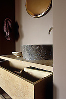 A round stone basin sits on top of  a simple wooden washstand with drawer