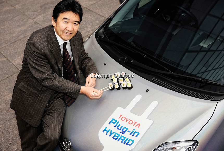 Yutaka Matsumoto, project general manager of Toyota Motor Corp.'s Strategy Planning Dept.'s R&D management center, eats sushi rolls off the bonnet of one of the automaker's ultra-clean plug-in hybrid vehicles at the company's headquarters in Tokyo, Japan on Tuesday 11 March 2009.