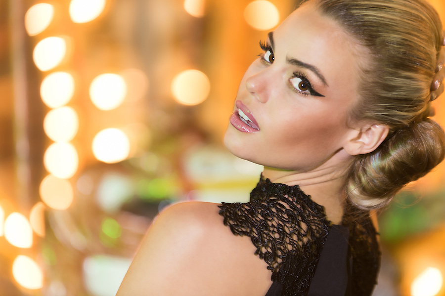 Closeup portrait of a beautiful gorgeous blond woman at a party in a stylish black dress looking back at the camera over her shoulder with parted lips