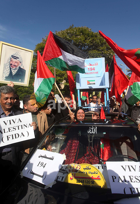 Palestinians take part in a rally in support of the efforts of President Mahmoud Abbas (pictured in poster) to secure a diplomatic upgrade at the United Nations, in Gaza City November 29, 2012. The U.N. General Assembly is set to implicitly recognize a sovereign state of Palestine on Thursday despite threats by the United States and Israel to punish the Palestinian Authority by withholding much-needed funds for the West Bank government. Photo by Ashraf Amra