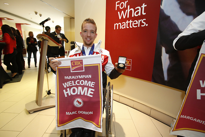 Ottawa, ON - March 28 2014 - Sochi 2014 Paralympic Games bronze medallist Marc Dorion of the sledge hockey team displays his limited edition gold-plated coin and personalized Welcome Home banner at the CIBC Paralympic Welcome Home Event at CIBC South Keys Banking Centre in Ottawa (Photo: Patrick Doyle/CIBC)