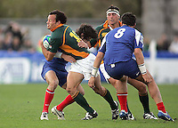 South African centre Francois Hougaard is tackled by French full back Mathieu Belie during the Division A U19 World Championship clash at Ravenhill.