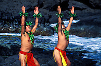 Two male hula kahiko dancers wearing the traditional red malo (loincloth) raise their arms to the sky. Shot by the surf with rocky background at Richardson Ocean Park in Hilo on the Big Island of Hawaii.