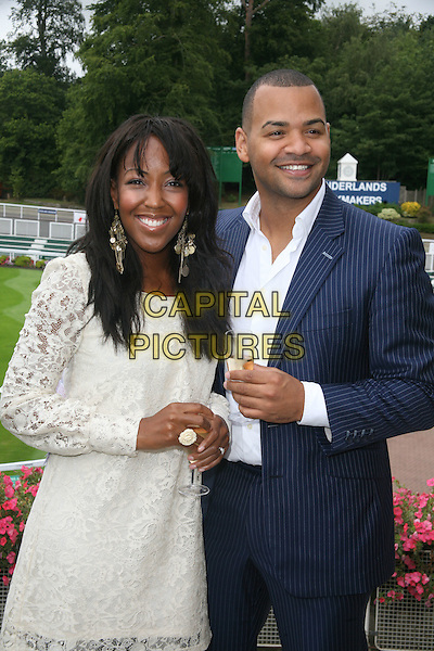 ANGELLICA BELL & MICHAEL UNDERWOOD .Variety Club of Great Britain Race Day, Sandown Park, Esher, Surrey, England, UK, 21st August 2010..half length white cream lace dress earrings dangly glass ring rings drink blue suit shirt jacket jacket .CAP/DS.©Dudley Smith/Capital Pictures