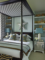 In the master bedroom the fabric of the curtains has also been used to line the canopy of the four-poster bed