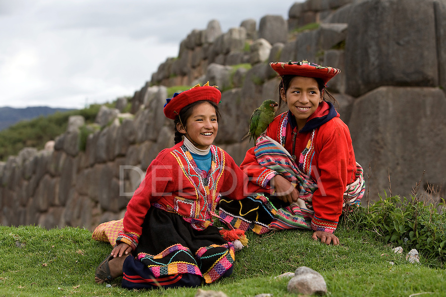 Two young Peruvian sisters, dressed in traditional clothing with their pet parrot, pose for photographs for tourists outside some Inca ruins near Cuzco, Peru.
