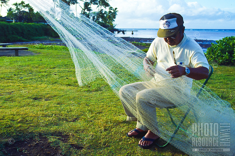A  local fisherman takes time to repair a damaged net after bringing in a successful catch.  Oahu.