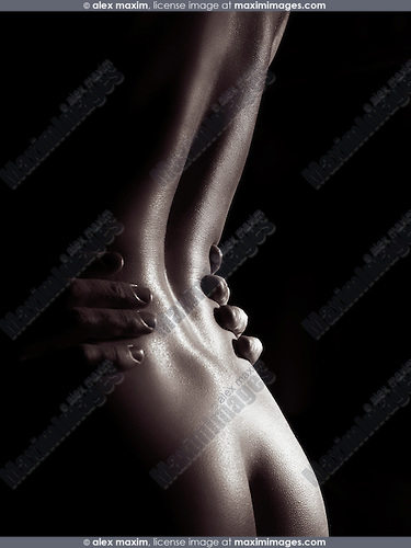 Artistic nude closeup of a sexy nude woman body with man hands on her waist, black and white fine art body parts abstract photo