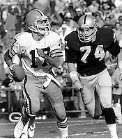Cleveland QB Brian Sipe is chased by Oakland Raider lineman Dave Pear. (1979 photo by Ron Riesterer)