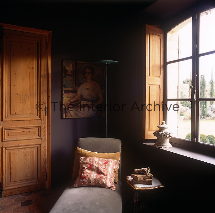 The corner of an aubergine room with a window with wooden shutters. A floor lamp stands behind a simple chaise longue upholstered in grey fabric.