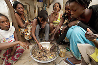 Senegal. Dakar. Marie (second from left) eats thieboudienne at lunch with her friends. Thieboudienne is a traditional dish from Senegal, made from marinated fish cooked with tomato paste, rice, a variety of vegetables, onions and peanut oil. The name of the dish comes from Wolof, meaning rice and fish. Marie and her friends are all sex workers. They have been approched by ENDA Sante within the programme framework of the Global Fund and ANCS (Alliance Nationale contre le Sida). ENDA Sante is in charge of the component Advocacy prevention and care of vulnerable groups, such as sex workers, in a fight towards HIV Aids. The Global fund supports ANCS and ENDA Sante with a financial grant. 08.12.09  © 2009 Didier Ruef