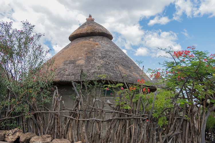 Circular thatched stone huts surrounded by protective stone walls or rustic wood fencing, are characteristic of the Konso villages found in the basalt hills of southern Ethiopia.