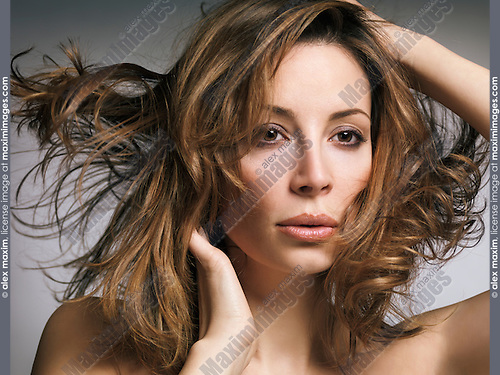 Beauty portrait of a woman with flying light brown hair and natural makeup in her early thirties on gray background