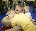 Major Ron Wier of Lakewood, Wash., and from the Idaho-based Army National Guard's 116th Cavalry Brigade Combat Team, hugs his boys, (left to right) Travis, 4, Kyle, 12, and Andru, 6, on Sunday Oct. 23, 2005 after  welcome home ceremonies at Ft. Lewis, Wash. Wier is part of an advance group of 302 soldiers from Idaho, Utah, Oregon, and North Dakota that will be remaining at Ft. Lewis to work in the demobilization process of the rest of the returning 4,000 members of the 116th Cavalry Brigade. ( AP PHOTO/Jim Bryant)