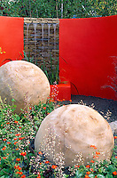 A rendered red wall with a drystone waterfall and two enormous hand-carved wooden balls dominate this garden