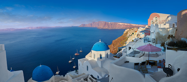 Panoramic of traditional blue domed Greek Orthodox church of Oia, Island of Thira, Santorini, Greece.