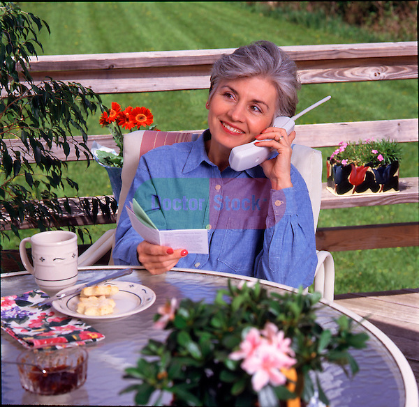 woman in telephone conversation while sitting on suburban patio