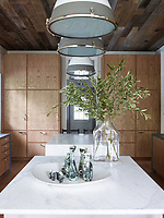 There are time-honoured materials in the kitchen, such as the twin islands sheathed in statuary marble. The kitchen's cupboards are clad in a wormy chestnut that has been brushed with a faint white wash and embellished with handsome burnished-nickel pulls. The pendant lights are from Ann-Morris Antiques  and the ceiling is covered in reclaimed barn siding.
