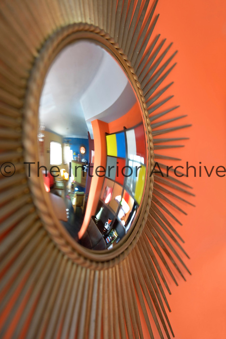 The living room is reflected in the convex glass of the sunburst mirror on a wall of the dining area