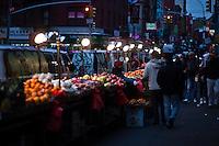 People cross by fruits displayed for customers at Manhattan's Chinatown in New York, Nov 11, 2013. VIEWpress/Eduardo Munoz Alvarez