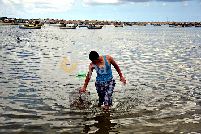 A Palestinian fisherman casts his net at Gaza's seaport in Gaza City on Sep. 06 2014. Israel and Hamas accepted an Egyptian proposal for a long-term ceasefire in war-torn Gaza. Restrictions imposed on Gaza fishermen are to be relaxed, with an immediate extension of the fishing zone to six nautical miles from the shore, to be extended later to 12 miles. Photo by Mohammed Talatene