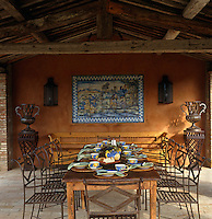A wooden dining table laid for lunch in the loggia with latticed iron chairs