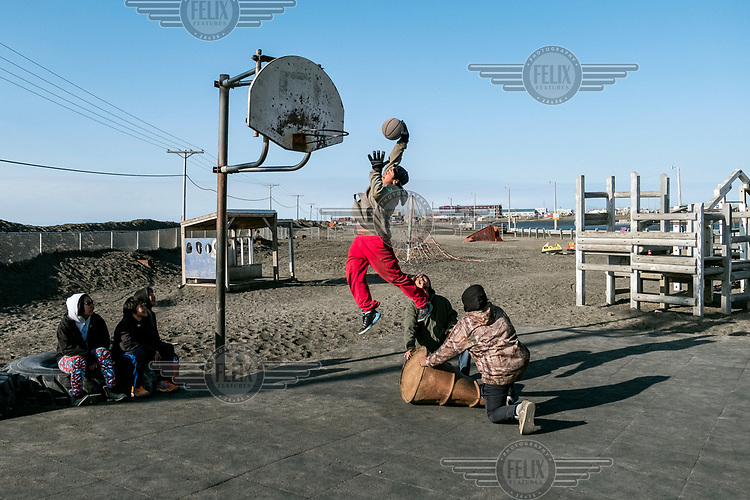 A group of Inupiat teenagers playing basketball.