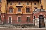 A woman with her dog walks by a brick building with red and yellow decorations on the facade in Como, Italy
