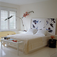 The double bedroom has louvered shutters and a large artwork in the place of a bedhead