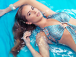 Beauty portrait of young woman in blue swimsuit lying in water Image © MaximImages, License at https://www.maximimages.com