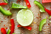 Raw Tilapia Covered in Green peppers, Red Peppers and a single lime in the middle