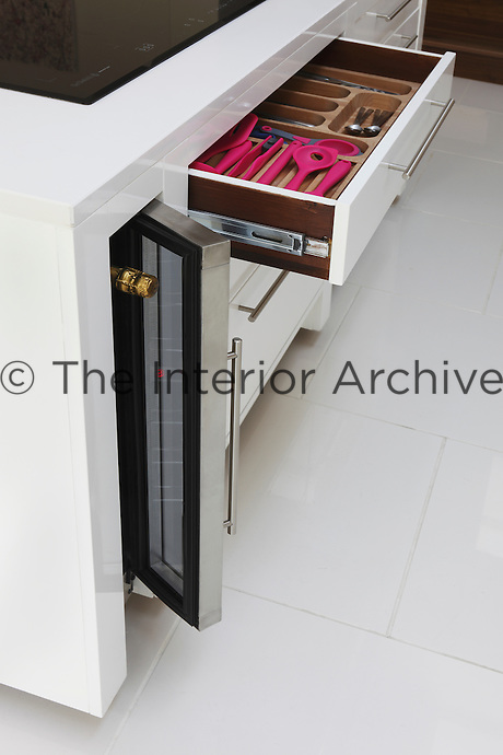 The kitchen island is furnished with a mini wine cooler and drawers filled with colour co-ordinated kitchen utensils