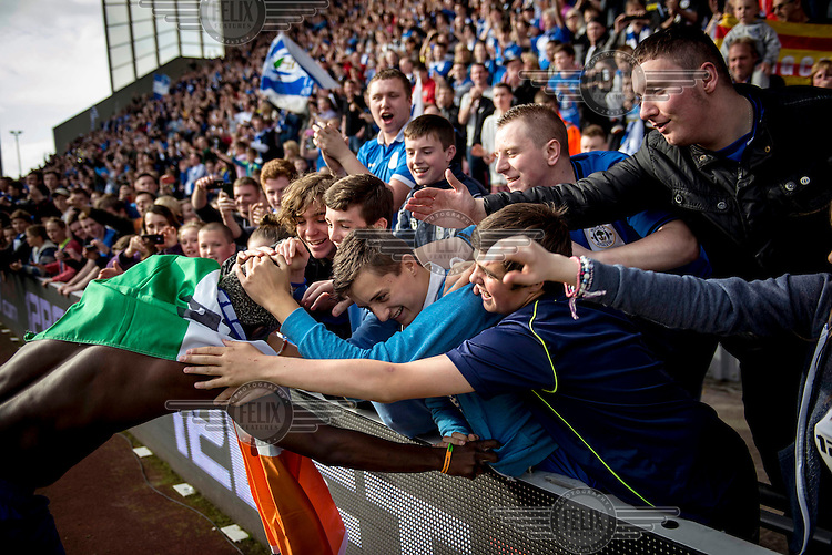 Wigan Football Club fans hug striker Arouna Kone at the end of a match at the club's DW Stadium. /Felix Features