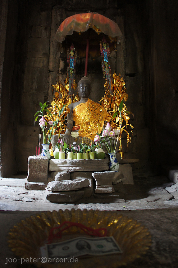 Buddha with saffron umbrella and dollar bill in donation plate, Angkor Wat, Cambodia, August 2011