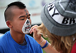 Chelsea Phillips paints Duy Nguyen's face at the Boys and Girls Club of Western Nevada booth at the 11th annual National Night Out hosted by the Carson City Sheriff's Office in Carson City, Nev., on Tuesday, Aug. 6, 2013. <br />