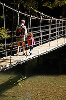 Mother and daughter crossing suspension bridge over Ohanapecosh River, Grove of the Patriarchs Trail, Mount Rainier National Park, Washington, USA