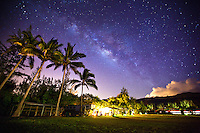 The Milky Way arches over the Mokuleia polo field at night, Camp Mokule'ia, O'ahu; a fireplace near a horse trailer offers illumination.