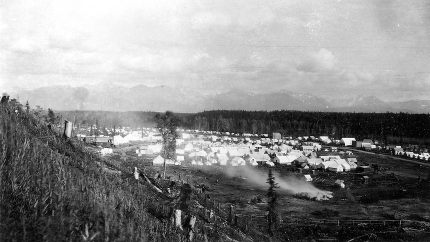 View of the temporary railroad construction town consisting of tents and a few buildings along Ship Creek in Anchorage, Alaska, 1915.  Identifiable businesses in the image include: The Crest House, Sourdough Lodging, and Montana Pool Room. Note the recently cut tree stumps on the slope in the foreground and the smoke from the burning pile of brush in the lower right. This image was probably taken within a few days of Capps arrival in Anchorage on June 14, 1915.  Photo by S.R. Capps, 1915, U.S Geological Survey Photo Library.
