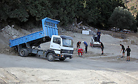Pictured: A tipper lorry unloads soil from the second site to the farmhouse plot so that it can be searched by specialist officers in Kos, Greece. Monday 10 October 2016<br />