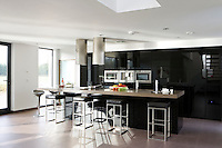 In the kitchen/living area the pale grey stone floors reflect light flooding in from generous floor-to-ceiling windows and a glass door leading to the garden