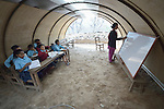 Principal Lal Maya Ale teaches a class in a temporary classroom at the Shri Pashupati Praja Primary School in the village of Tanglichowk, in the Gorkha District of Nepal. In the aftermath of the April 2015 earthquake that ravaged Nepal, the ACT Alliance helped people in this village with a variety of services, including latrines, emergency shelter, livelihood projects and school construction.