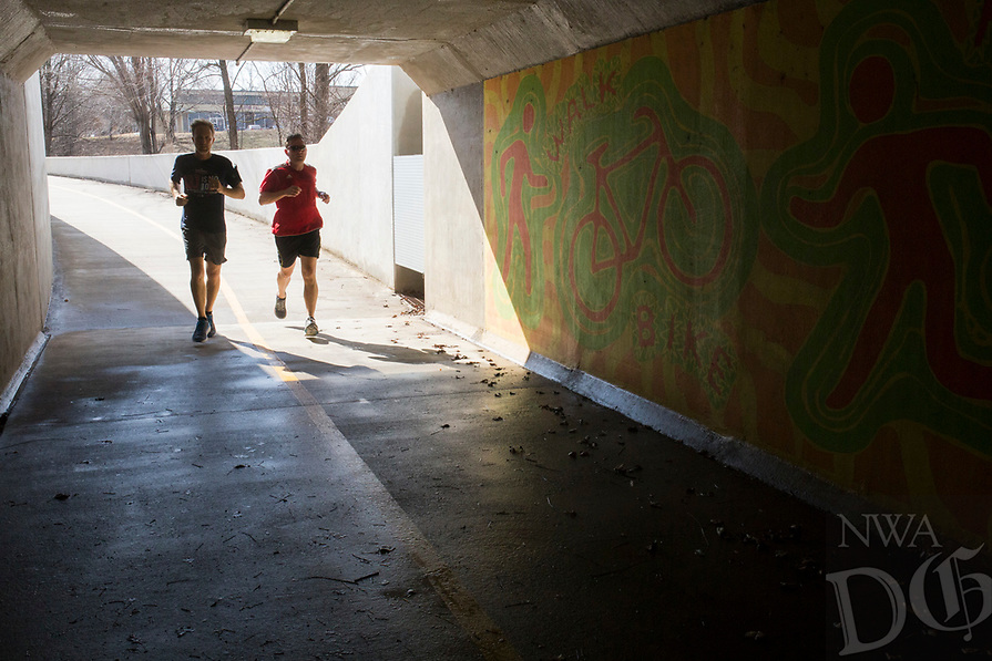 NWA Democrat-Gazette/CHARLIE KAIJO Joggers make their way through a tunnel on a bike path, Thursday, February 15, 2018 at the Razorback Greenway in Bentonville. <br />