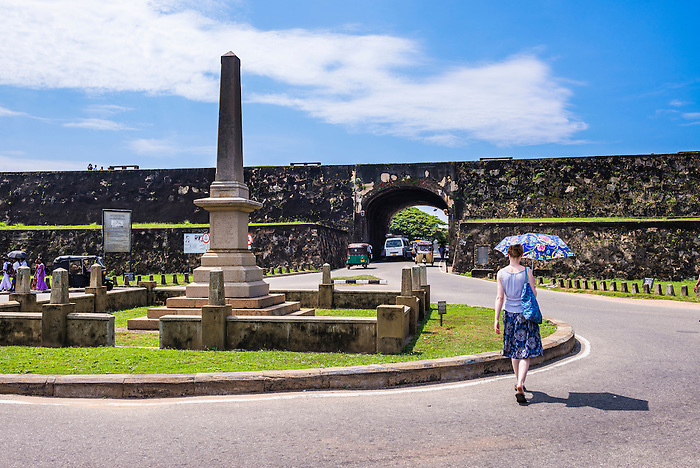 Tourist at the war memorial at the entrance to the Old Town of Galle and its Fortifications, South Coast of Sri Lanka, Asia. This is a photo of the war memorial at the entrance to the Old Town of Galle and its Fortifications, South Coast of Sri Lanka, Asia.