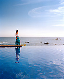 MEXICO, Baja, side view of a woman standing at the edge of an infinity pool, Esperanza Hotel