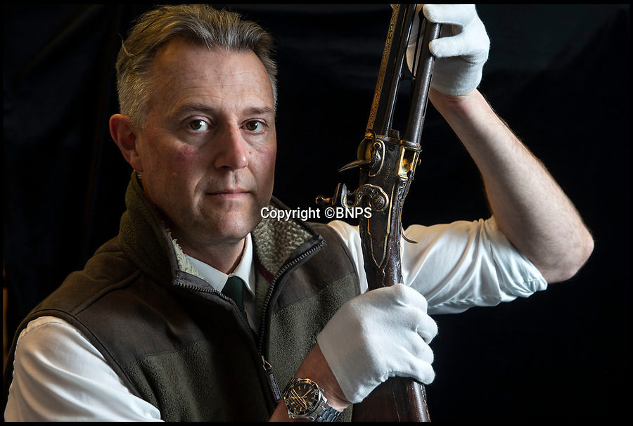 BNPS.co.uk (01202) 558833<br /> Pic: PhilYeomans/BNPS<br /> <br /> 'Once in a lifetime find' Auctioneer Anthony Cribb with the Tiger of Mysore's battle damaged flintlock musket.<br /> <br /> Stunning artefacts from Indian hero Tipu Sultan's fateful last stand have been rediscovered by the family of an East India Company Major who took part in the famous battle that ended his reign.<br /> <br /> And now Major Thomas Hart's lucky descendents are likely to become overnight millionaires after retrieving the historic items from their dusty attic.<br /> <br /> The fascinating treasures were taken from Tipu's captured fortress of Seringapatam in the wake of his defeat by British forces led by a young Duke of Wellington in 1799.<br /> <br /> The cache of ornate gold arms and personal effects even include's the battle damaged musket the Sultan used in his fatal last stand against the expanding British Empire in India.<br /> <br /> Tipu was last seen on the battlements of the fortress firing his hunting musket at the advancing British and after the fierce encounter his body was found bearing many wounds, including a musket ball shot above his right eye.<br /> <br /> The rediscovered musket, complete with battle damaged bayonet, has the distinctive tiger stripe pattern unique to the self styled Tiger of Mysore own weapons - and tellingly there is also shot damage to the lock and stock that may have been caused by the musket ball that finished him off.<br /> <br /> Also included in the sale are four ornate gold-encrusted sword's bearing the mark of Haider Ali Khan, Tipu's father and the previous ruler of independent Mysore, along with a solid gold 'betel casket' complete with three 220 year old nuts still inside.<br /> <br /> The war booty was brought back to Britain by Major Thomas Hart of the British East India Company following the fourth and final Anglo-Mysore war.<br /> <br /> They have been passed down through the family ever since and now belong to a couple who have kept them wrapped in newspaper in the dusty attic of their semi-detached home for years.