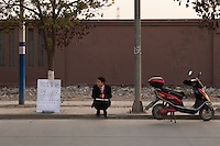 Daytime landscape view of a real estate salesman squatting on a curb in near Songjiang, China.  © LAN