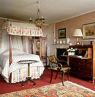 This guest bedroom is furnished with a large mahogany desk and a four-poster bed