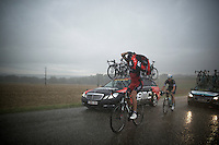 Daniel Oss (ITA/BMC) (trying to) putting on a rain jacket in a full blown thunderstorm.<br /> Mark Reshaw (AUS/Omega Pharma-Quickstep) doesn't even try putting on the jacket...<br /> <br /> 2014 Tour de France<br /> stage 19: Maubourguet - Bergerac (208km)