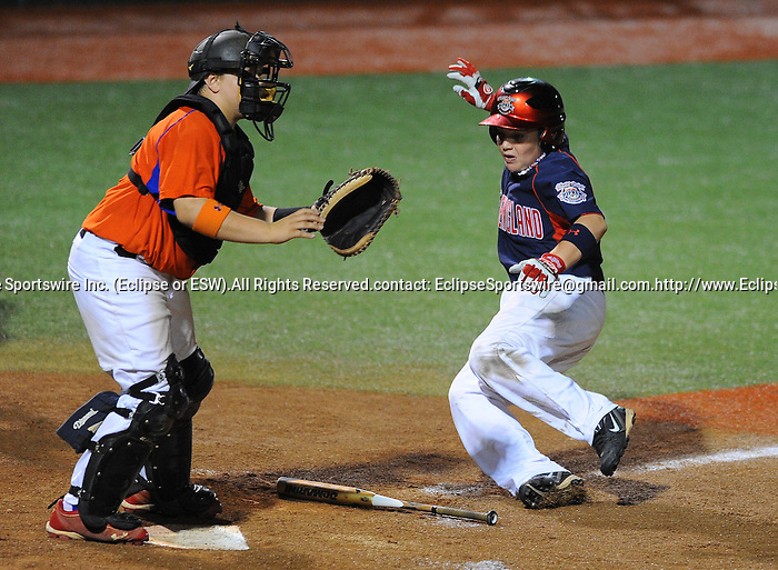 Newtown(CT)'s Lucas O'Brien tries to avoid the bat and slide safely for the run while taking out Forest Hill(MD)'s Sean D'Adamo during the All Star Game at the Cal Ripken Babe Ruth World Series in Aberdeen, Maryland on August 16, 2012 featuring Team Bambino and Team Ironman comprised of players from all the teams that did not advance to the playoffs. Team Ironman (Longview(WA), Newtown(CT), Little Rock(AR) and Canada) defeated Team Bambino (Mattoon(IL), Lamar(CO), Harford County and Australia) 4 to 3.