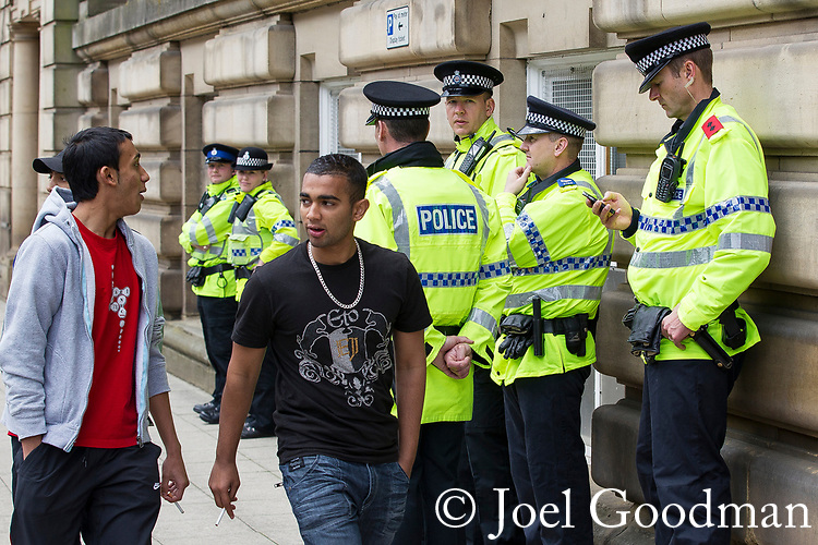 © Joel Goodman - 07973 332324 . 24/06/2011 . Blackburn, UK . Police stand guard as supporters of EDL leader Tommy Robinson ( aka Stephen Yaxley-Lennon ) demonstrate outside Blackburn Magistrates Court as Robinson faces his first appearance related to charges for an assault at an EDL demonstration in Blackburn on 2nd April 2011 . Photo credit : Joel Goodman